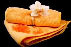 Fleurissez les orchidées jaune-orange et la serviette orange sur le Ba noir brillant Image libre de droits