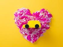 Fleurissez les pétales dans la forme de coeur et la voiture de jouet Photo libre de droits