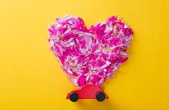 Fleurissez les pétales dans la forme de coeur et la voiture de jouet Photos stock