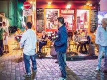 Fleurissez les vendeurs devant le café bien allumé, soirée, Montmartre, Paris Photographie stock libre de droits