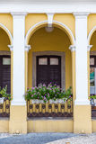 Fleurissez sur le balcon au bâtiment antique jaune de style Image libre de droits