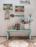 Fleurissez sur le banc vert avec le mur en bois blanc de panneau Photo libre de droits