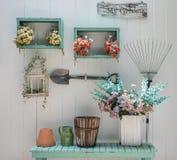 Fleurissez sur le banc vert avec le mur en bois blanc de panneau Image stock