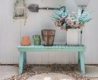 Fleurissez sur le banc vert avec le mur en bois blanc de panneau Photos libres de droits