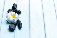 Fleurissez sur le groupe de la pierre noire sur le plancher en bois Photographie stock libre de droits