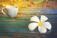 Fleurissez sur le vieux plancher en bois avec la tasse de café Photos stock