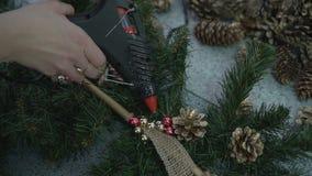 Fleuriste à l'aide de l'arme à feu de colle pour la décoration de branche de Noël banque de vidéos
