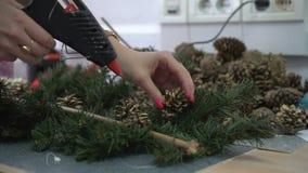 Fleuriste à l'aide de l'arme à feu de colle pour la décoration de guirlande de Noël clips vidéos