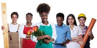 Fleuriste africain riant avec le groupe d'autres apprentis internationaux photos stock