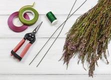 Fleuriste au travail : étapes de faire la guirlande de porte de Bruyère de bruyère dedans Photos stock