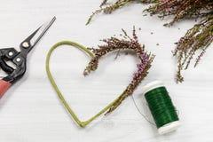 Fleuriste au travail : étapes de faire la guirlande de porte de Bruyère de bruyère dedans Photo stock