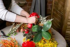 Fleuriste au travail : Comment faire une pièce maîtresse de thanksgiving avec le grands potiron et bouquet des fleurs Point par p images stock