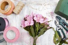 Fleuriste au travail : femme s'chargeant du bouquet des fleurs d'alstroemeria Photographie stock libre de droits