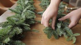 Fleuriste au travail : la femme remet faire la guirlande de décorations de Noël du sapin Nobilis Festin de dîner de bonne année banque de vidéos