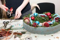 Fleuriste au travail sur une guirlande de Noël pour les vacances Photos libres de droits