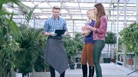 Fleuriste communiquant avec des clients en serre chaude banque de vidéos
