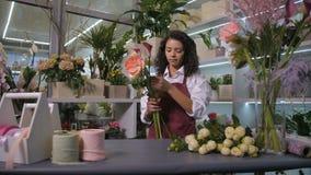 Fleuriste de femme faisant le groupe des fleurs à l'atelier banque de vidéos