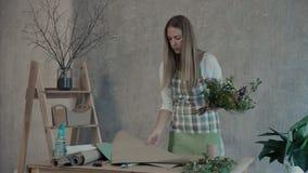 Fleuriste enveloppant des fleurs en papier au fleuriste banque de vidéos