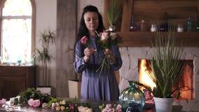 Fleuriste féminin à cheveux longs dans la robe bleue jugeant une moitié faite bouquet et ajoutant des fleurs et des plantes à la  banque de vidéos