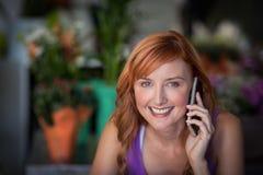 Fleuriste féminin à l'aide du téléphone portable Images stock