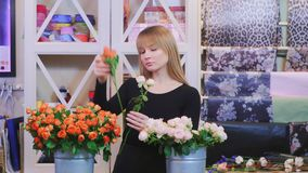 Fleuriste féminin arrangeant des roses dans le fleuriste banque de vidéos