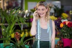 Fleuriste féminin parlant au téléphone portable Image stock