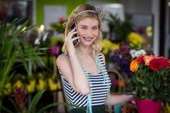 Fleuriste féminin parlant au téléphone portable Image libre de droits