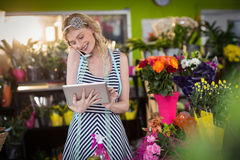 Fleuriste féminin parlant au téléphone portable et à l'aide du comprimé numérique Photo libre de droits