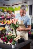 Fleuriste masculin arrangeant des fleurs Images stock