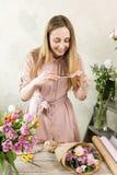 Fleuriste photographiant le bouquet au téléphone Images stock
