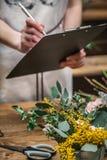 Fleuriste prenant des notes fonctionnant dans la boutique photos stock