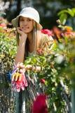 Fleuristes de sourire de jeune femme dans le fonctionnement de tablier photographie stock