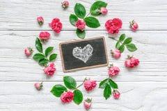 Fleurit la composition le cadre fait en rose de rose fleurit avec le symbole de coeur sur le tableau Photos stock