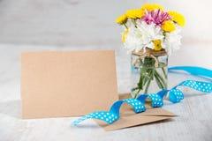 Fleurit le bouquet dans un vase à pot avec la note de carte, l'enveloppe et le ruban bleu sur un fond rustique en bois blanc Photo libre de droits