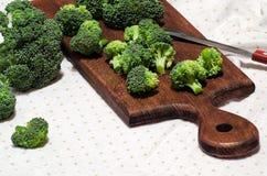Fleurons de brocoli sur un panneau et un couteau de cuisine Images stock