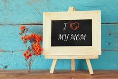 Fleurs à côté de tableau noir avec l'expression : J'AIME MA MAMAN, sur la table en bois Concept heureux du jour de mère Photos libres de droits