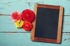 Fleurs à côté de tableau noir vide Image stock