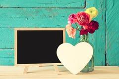 Fleurs à côté de tableau noir vide, sur la table en bois Photos stock