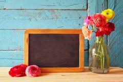Fleurs à côté de tableau noir vide, sur la table en bois Copiez l'espace Photo stock