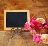 Fleurs à côté de tableau noir vide, sur la table en bois Copiez l'espace Photographie stock libre de droits