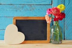 Fleurs à côté de tableau noir vide, sur la table en bois Copiez l'espace Images libres de droits