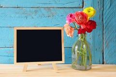 Fleurs à côté de tableau noir vide, sur la table en bois Copiez l'espace Images stock