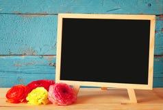 Fleurs à côté de tableau noir vide, sur la table en bois Copiez l'espace Photos libres de droits