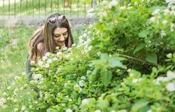 Fleurs admiratives de belle fille Photographie stock libre de droits