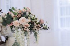 Fleurs artificielles élégantes dans un support en verre de vase sur un plancher image stock