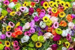 Fleurs artificielles multicolores colorées de fond petites à un b Photos  stock