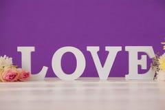 Fleurs avec des alphabets formant l'amour sur la table Photos libres de droits