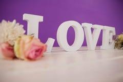 Fleurs avec des alphabets formant l'amour sur la table Image libre de droits