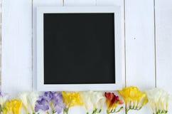 Fleurs avec le cadre de tableau noir vide de tableau sur un fond en bois clair Photo romantique Images stock