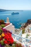 Fleurs, bâtiments et bateau de croisière à Oia, Santorini Image stock